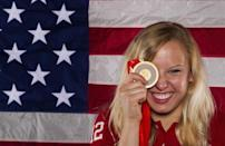Paralympic swimmer Jessica Long holds up a gold medal as she poses for a portrait during the 2012 U.S. Olympic Team Media Summit in Dallas, May 13, 2012. Long won the gold medal in the Women's 100m Butterfly during the 2008 Beijing Paralympic Games.