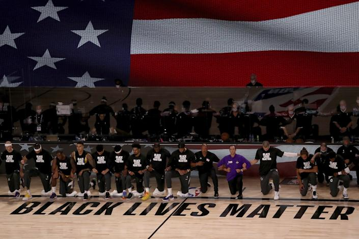 "Lakers and Clippers wear Black Lives Matter shirts and kneel during the national anthem before their first game in the Orlando bubble on July 30. <span class=""copyright"">(Mike Ehrmann / Associated Press)</span>"