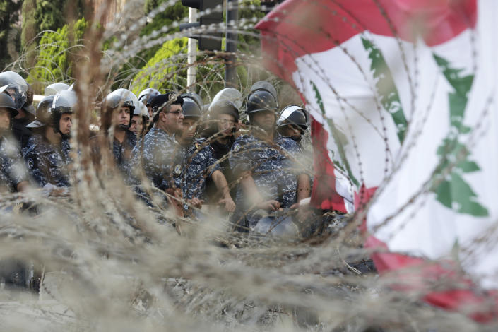 Police stand behind barricades that were installed as extra security measures around the Lebanese government building in Beirut, Lebanon, Saturday, Oct. 19, 2019. The blaze of protests was unleashed a day earlier when the government announced a slate of new proposed taxes, including a $6 monthly fee for using Whatsapp voice calls. The measures set a spark to long-smoldering anger against top leaders from the president and prime minister to the numerous factional figures many blame for decades of corruption and mismanagement. (AP Photo/Hassan Ammar)