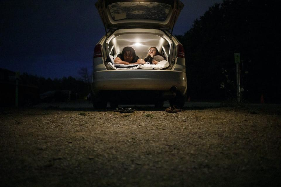Two young people at a drive-in theatre.