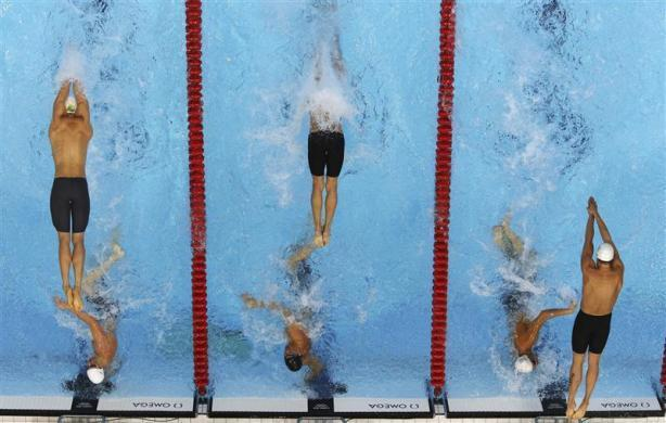 Swimmers from Australia (L), the U.S. (C) and France compete during the men's 4 x 100m freestyle relay final at the London 2012 Olympic Games at the Aquatics Centre July 29, 2012.