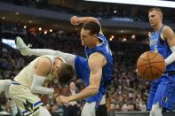 Dallas Mavericks' Dwight Powell is fouled by Milwaukee Bucks' Kyle Korver during the first half of an NBA basketball game Monday, Dec. 16, 2019, in Milwaukee. (AP Photo/Morry Gash)