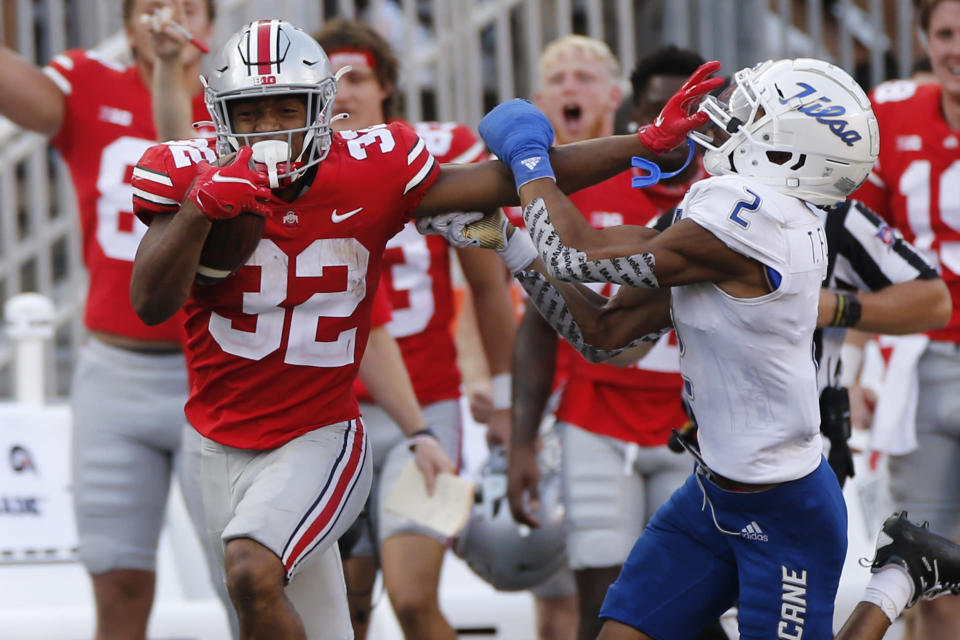 Ohio State running back TreVeyon Henderson, left, stiff-arms Tulsa defensive back Travon Fuller during the second half of an NCAA college football game Saturday, Sept. 18, 2021, in Columbus, Ohio. (AP Photo/Jay LaPrete)