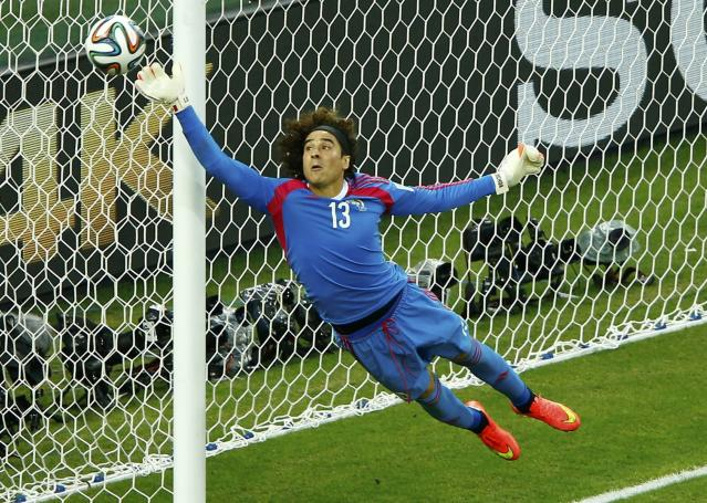 Mexico's Guillermo Ochoa jumps to save the ball during their 2014 World Cup Group A soccer match against Brazil at the Castelao arena in Fortaleza, June 17, 2014. REUTERS/Mike Blake (BRAZIL - Tags: SOCCER SPORT WORLD CUP TPX IMAGES OF THE DAY)