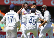 India's Mohammed Siraj, second left, celebrates with teammates after dismissing Australia's David Warner during play on the first day of the fourth cricket test between India and Australia at the Gabba, Brisbane, Australia, Friday, Jan. 15, 2021. (AP Photo/Tertius Pickard)