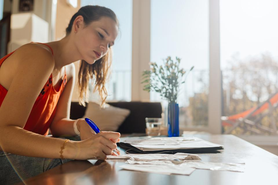 Woman doing bookkeeping at home at a sunny afternoon.