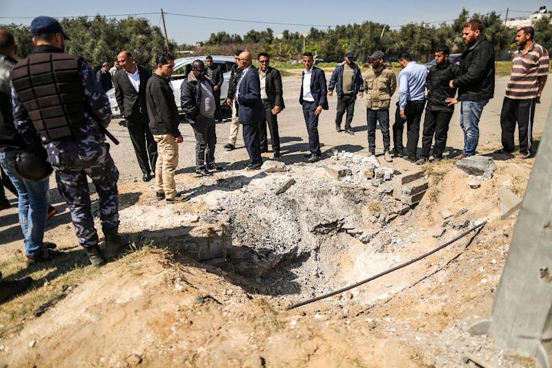 Hamas security force members inspect the crater left by a bomb that targeted the convoy of Palestinian prime minister Rami Hamdallah on a rare visit to the Gaza Strip on March 13, 2018 (AFP Photo/MAHMUD HAMS)