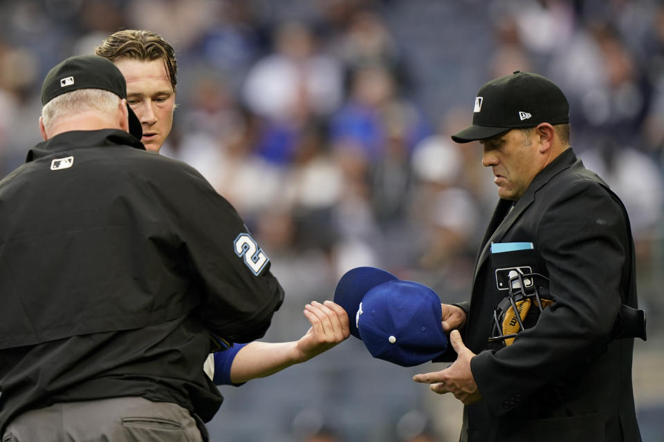 Third base umpire Bill Miller, left, and home plate umpire Brian Knight inspect the cap and glove of Kansas City Royals starting pitcher Brady Singer for foreign substances after Singer pitched the first inning of a baseball game against the New York Yankees, Tuesday, June 22, 2021, at Yankee Stadium in New York. (AP Photo/Kathy Willens)