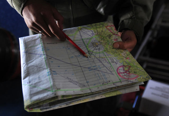 A pilot of a Royal Malaysian Air Force CN-235 aircraft shows a map during a search and rescue operation for the missing Malaysia Airlines plane over the waters at Malacca straits, Malaysia, Thursday, March 13, 2014. Planes sent Thursday to check the spot where Chinese satellite images showed possible debris from the missing Malaysian jetliner found nothing, Malaysia's civil aviation chief said, deflating the latest lead in the six-day hunt. The hunt for the missing Malaysia Airlines flight 370 has been punctuated by false leads since it disappeared with 239 people aboard about an hour after leaving Kuala Lumpur for Beijing early Saturday. (AP Photo/Lai Seng Sin)