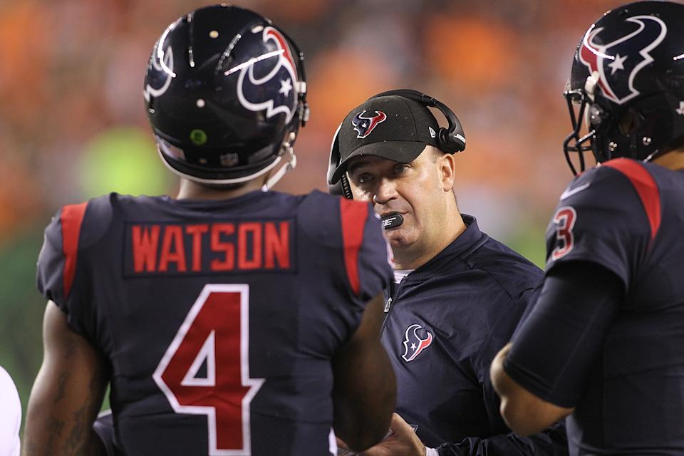 Bill O'Brien talks to Deshaun Watson and Tom Savage on the sideline during a game.