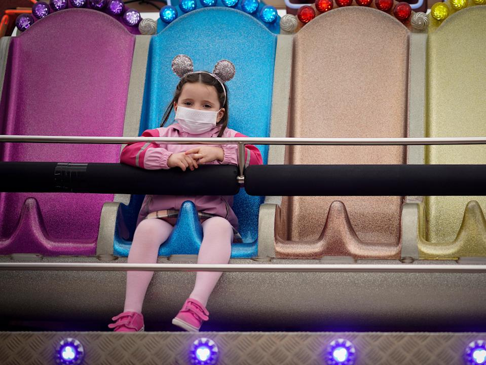 <p>A young girl wearing a mask at a Blackpool fairground</p> (Getty)