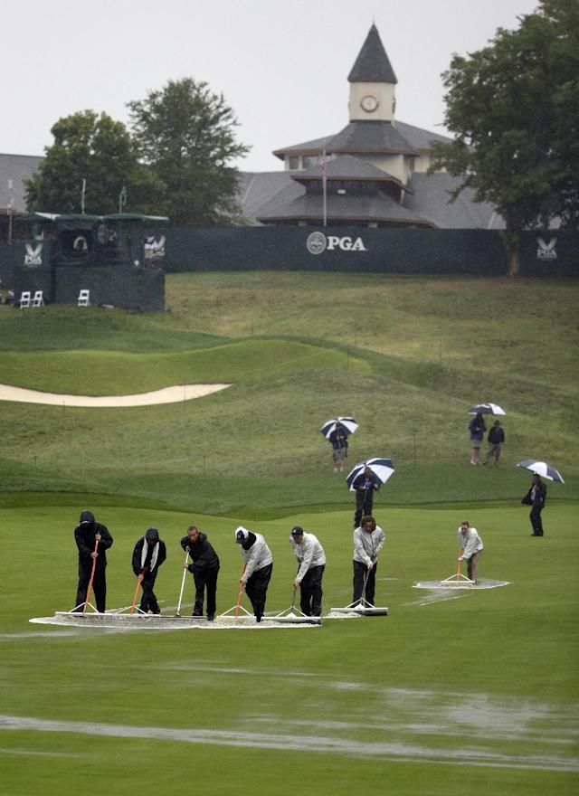 Members of the grounds crew push water off the first fairway during the second round of the PGA Championship golf tournament at Valhalla Golf Club on Friday, Aug. 8, 2014, in Louisville, Ky. (AP Photo/John Locher)