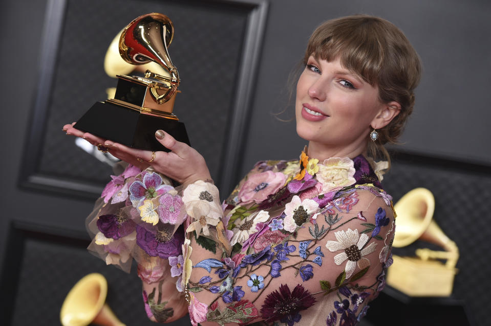 Taylor Swift poses in the press room with the award for album of the year for