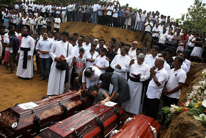 A woman reacts next to two coffins during a mass burial of victims, two days after a string of suicide bomb attacks on churches and luxury hotels across the island on Easter Sunday, at a cemetery near St. Sebastian Church in Negombo, Sri Lanka, April 23, 2019.  (Photo: Athit Perawongmetha/Reuters)
