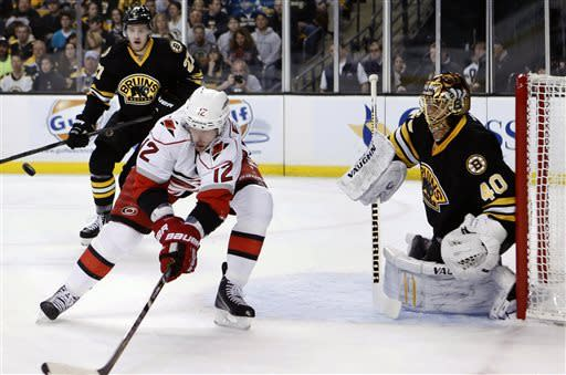 Carolina Hurricanes' Eric Staal (12) reaches for control of the puck in front of Boston Bruins' Tuukka Rask (40) in the first period of an NHL hockey game in Boston, Monday, April, 8, 2013. (AP Photo/Michael Dwyer)