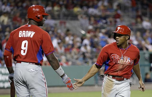 Philadelphia Phillies' Ben Revere, right, is greeted by teammate Domonic Brown (9) after scoring on an RBI-single hit by Marlon Byrd in the fifth inning of an exhibition spring baseball game against the Boston Red Sox in Fort Myers, Fla., Saturday, March 15, 2014. (AP Photo/Gerald Herbert)