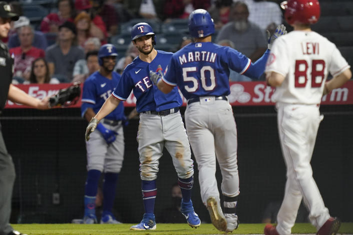 Texas Rangers' Jason Martin (50) celebrates with Nick Solak, center left, after hitting a home run during the second inning of a baseball game against the Los Angeles Angels Friday, Sep. 3, 2021, in Anaheim, Calif. Solak also scored. (AP Photo/Ashley Landis)