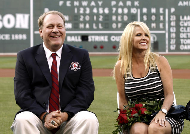 FILE - In this Aug. 3, 2012 file photo, former Boston Red Sox pitcher Curt Schilling sits with his wife Shonda, right, after being introduced as a new member of the Red Sox Hall of Fame before a baseball game between the Red Sox and the Minnesota Twins at Fenway Park in Boston. Schilling, whose video game company collapsed into bankruptcy, is selling off furniture, sports collectibles and even artificial plants from his Massachusetts home. An estate sale company has scheduled a sale of items from Schilling's seven-bedroom, 8,000-square-foot Medfield residence for Saturday, Oct. 12, 2013. (AP Photo/Winslow Townson, File)