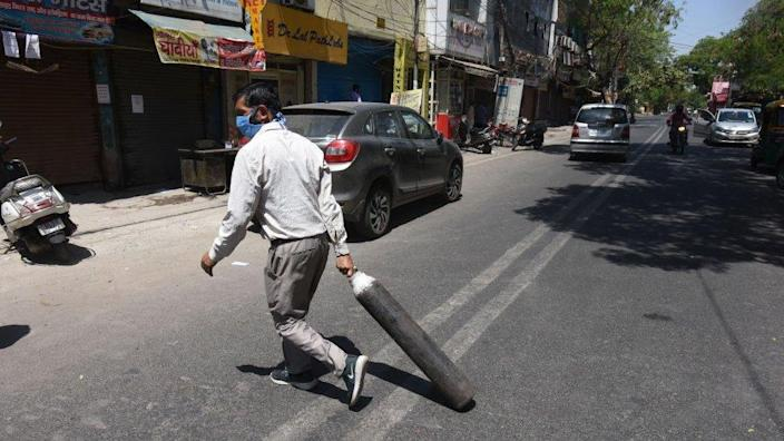 A family member of Covid-19 patient carries an empty cylinder to refill outside the oxygen filling centre at Dilshad Garden Area on April 25, 2021 in New Delhi, India.