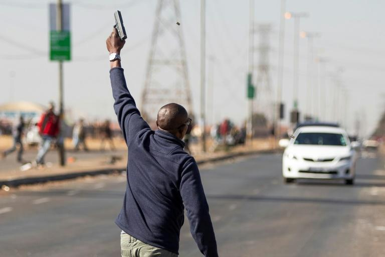 A man fires a gun in the air to disperse suspected looters outside a mall in the Johannesburg suburb of Vosloorus Unrest raged in South Africa on July 14, 2021, for the sixth day running, stoking fears of food and fuel shortages as disruption to farming, manufacturing and oil refining began to bite. Seventy-two people have died and more than 1,200 people have been arrested, according to official figures, since former president Jacob Zuma began a 15-month jail term, sparking protests that swiftly turned violent.
