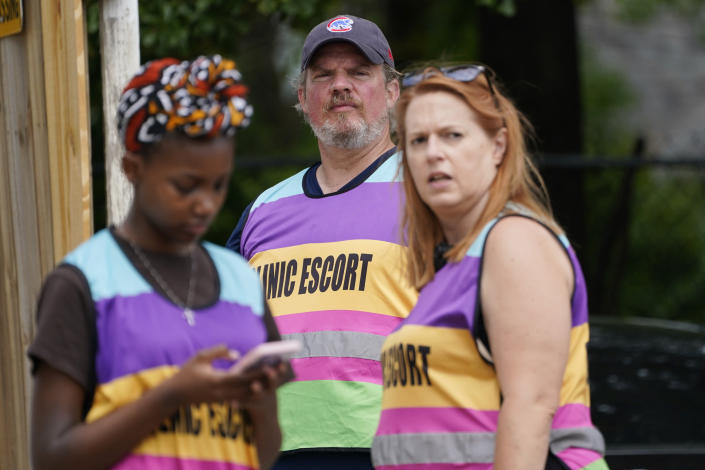 Clinic escorts James Parker, center, Asia Brown, left, and Kim Gibson, look out for vehicles entering the Jackson Womens Health Organization clinic parking lot, Thursday, May 20, 2021, in Jackson, Miss. The clinic is Mississippi's only state licensed abortion facility. On May 17, 2021, the U.S. Supreme Court agreed to take up the dispute over a Mississippi ban on abortions after 15 weeks of pregnancy. The issue is the first test of limits on abortion access to go before the conservative majority high court. Their decision could mean more restrictions, and focuses on the landmark 1973 ruling in Roe v. Wade, which established a woman's right to an abortion. (AP Photo/Rogelio V. Solis)