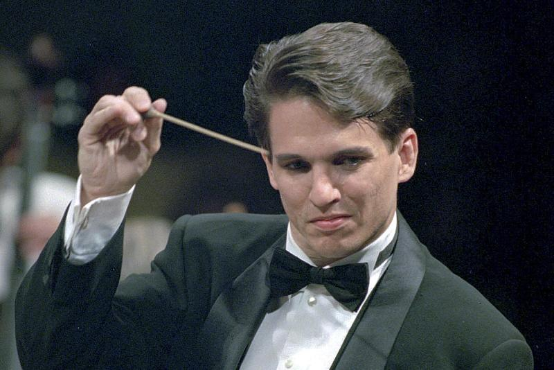 FILE - In this May 1995 file photo, Boston Pops Orchestra conductor Keith Lockhart wields the baton during a performance at Symphony Hall in Boston. Lockhart was just 35 when he took over as Pops conductor in 1995, and is marking 25 years in 2020, making him the orchestra's second longest-tenured conductor after Arthur Fiedler. (AP Photo/Julia Malakie, File)
