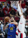 Denver Nuggets guard Austin Rivers, left, shoots next to Portland Trail Blazers center Jusuf Nurkic during the first half of Game 3 of an NBA basketball first-round playoff series Thursday, May 27, 2021, in Portland, Ore. (AP Photo/Craig Mitchelldyer)