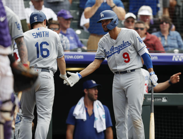 Los Angeles Dodgers' Kristopher Negron, right, congratulates Will Smith, who had hit a three-run home run off Colorado Rockies' Wade Davis during the ninth inning of a baseball game Wednesday, July 31, 2019, in Denver. The Dodgers won 5-1. (AP Photo/David Zalubowski)