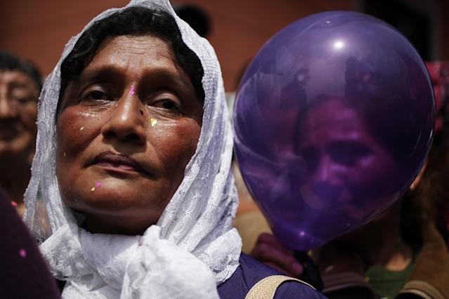 "<p>Women, one holding a balloon, attend a procession honoring ""The Lord of Miracles,"" the patron saint of Lima, in Lima, Peru, Oct. 18, 2012. (Photo: Rodrigo Abd/AP) </p>"