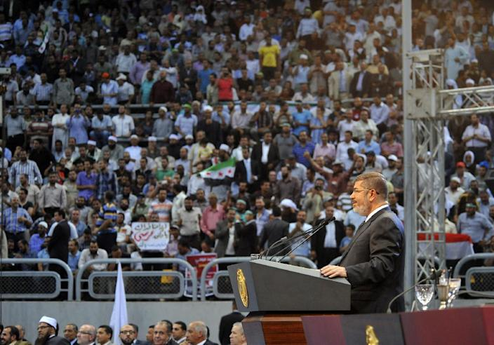 "In this image released by the Egyptian Presidency, Egyptian President Mohammed Morsi addresses a rally called for by hardline Islamists loyal to the Egyptian president to show solidarity with the people of Syria, in a stadium in Cairo, Egypt, Sunday, June 15, 2013. Egypt's Islamist president announced Saturday that he was cutting off diplomatic relations with Syria and closing Damascus' embassy in Cairo, decisions made amid growing calls from hard-line Sunni clerics in Egypt and elsewhere to launch a ""holy war"" against Syria's embattled regime. (AP Photo/Egyptian Presidency)"