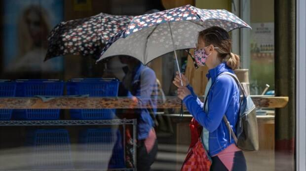 A pedestrian shields themselves from the sun as they walk through downtown Ottawa in late June. On Saturday, city health officials reported 14 new COVID-19 cases. (Brian Morris/CBC - image credit)
