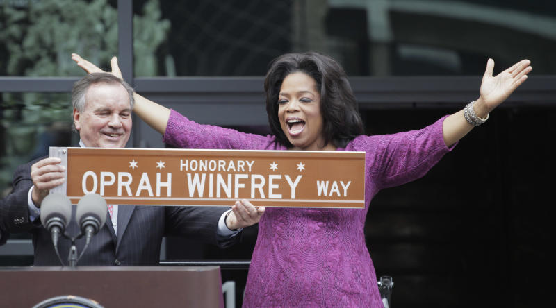 FILE-This May 11, 2011, file photo shows Chicago Mayor Richard M. Daley presenting TV talk-show host Oprah Winfrey with a sign after a street was named in her honor outside her Harpo Studios in Chicago. Winfrey is selling Harpo Studios in Chicago to a developer, but the studio will remain on the property for another two years. Harpo Inc. said in a statement that it has entered into a purchasing agreement with Sterling Bay Cos. for the four-building campus on Chicago's West Side. (AP Photo/M. Spencer Green, File)