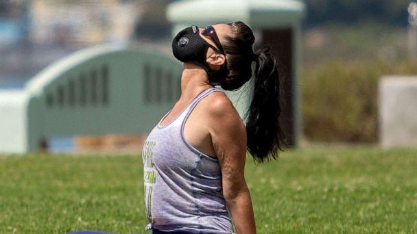 PHOTO: A woman wearing a facemask practices yoga at Bluff park in Long Beach, Calif., July 14, 2020. (Apu Gomes/AFP via Getty Images, FILE)