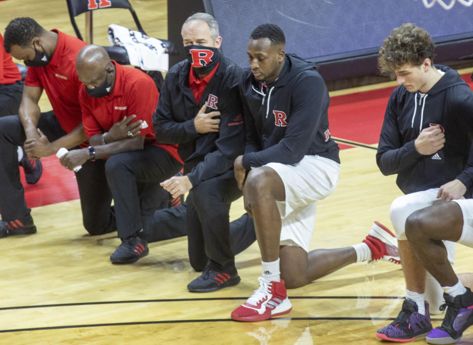 Rutgers coach Steve Pikiell, center, takes a knee with some of his staff and players during the national anthem inside an empty Rutgers Athletic Center before the team's NCAA college basketball game against Sacred Heart on Wednesday, Nov. 25, 2020, in Piscataway, N.J. (Andrew Mills/NJ Advance Media via AP)