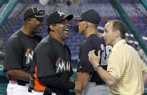 Miami Marlins manager Ozzie Guillen, second from left, laughs as he talks to New York Yankees general manager Brian Cashman, right, before a spring training baseball game in Miami, Sunday, April 1, 2012, as Yankees manager Joe Girardi, second from right, talks to Marlins batting coach Tony Perez, left. (AP Photo/Alan Diaz)