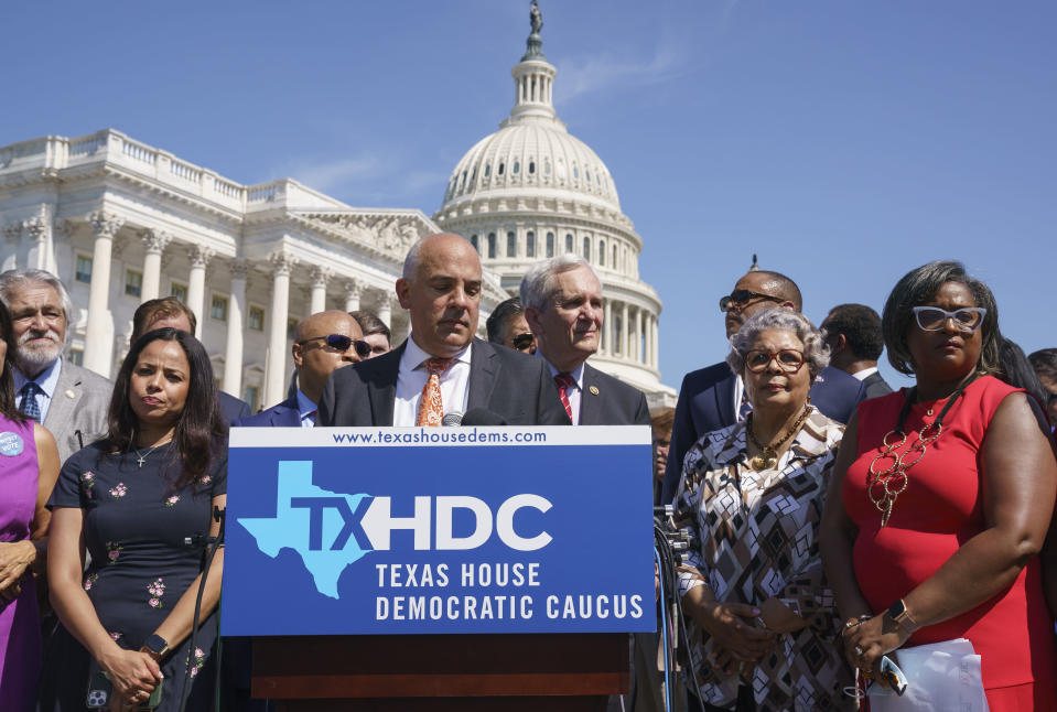 Rep. Chris Turner, chairman of the Texas House Democratic Caucus, center, is joined by Democratic members of the Texas legislature at a news conference at the Capitol in Washington, Tuesday, July 13, 2021, after they left Austin hope to deprive the Legislature of a quorum — the minimum number of representatives who have to be present for the body to operate. They are trying to kill a Republican bill making it harder to vote in the Lone Star State. (AP Photo/J. Scott Applewhite)