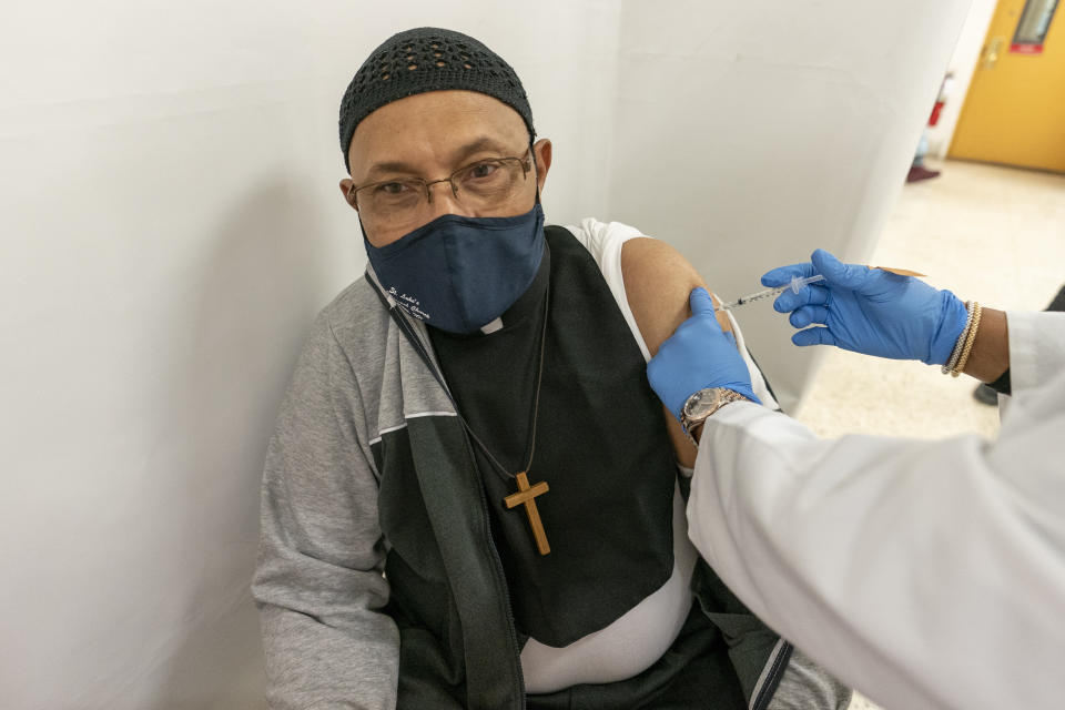 The Rev. David R. Steele, Associate Clergy at Luke's Episcopal church receives the first dose of the COVID-19 vaccination at a pop-up vaccination site at St. Luke's Episcopal Church, Tuesday, Jan. 26, 2021, in the Bronx borough of New York. (AP Photo/Mary Altaffer)