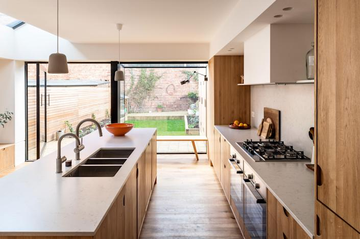 A single, massive pivot door opens the kitchen up to the backyard.