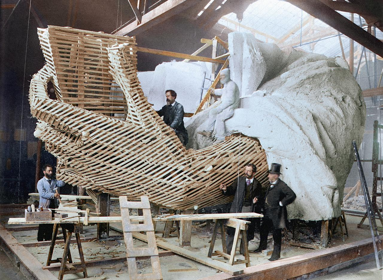 <p>Artists work on the left hand of the Statiue of Liberty in Paris, in 1881. The Roman goddess was built in France, in parts. (Head of Zeus Books) </p>