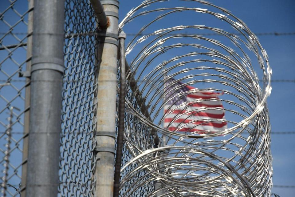 The American flag is seen behind barbed wire at Holman Correctional Facility in Atmore, Ala.