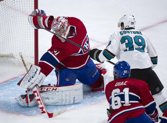 San Jose Sharks' Logan Coutrue, right, scores against Montreal Canadiens goaltender Carey Price, left, as Canadiens' Raphael Diaz (61) defends during the second period of an NHL hockey game in Montreal, Saturday, Oct. 26, 2013. (AP Photo/The Canadian Press, Graham Hughes)