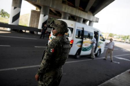 A military police officer observes traffic at an immigration checkpoint on a road in Tapachula