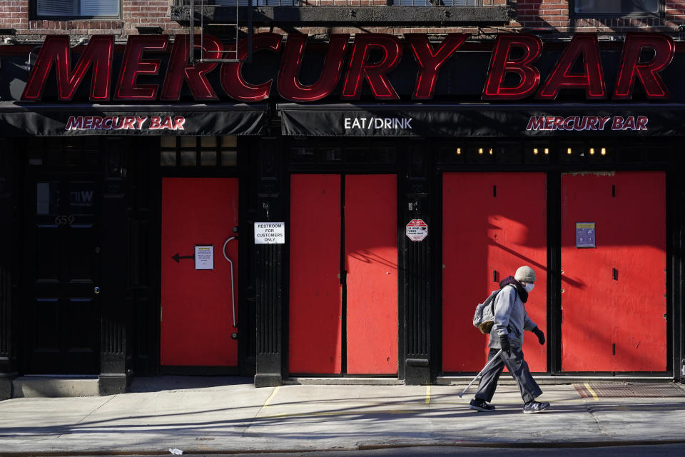 A pedestrian walks past a boarded-up bar, Sunday, Jan. 10, 2021, in the Hell's Kitchen neighborhood of New York. The boarded-up windows and For Rent signs are all over the place in Manhattan's Hell's Kitchen neighborhood. Nearby, the Broadway theaters are all dark. But the economic darkness brought on by the coronavirus pandemic has had a few bright spots. A couple of well-loved venues have gotten financial boosts, thanks to online fundraising campaigns and even a telethon. (AP Photo/Mary Altaffer)
