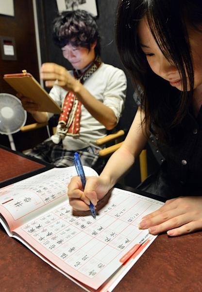 Akihiro Matsumura (L) uses his tablet computer as his friend practices writing Chinese characters in Tokyo on June 19, 2013. Like millions of people across East Asia, Matsumura is forgetting the pictographs and ideographs that have been used in Japan and greater China for centuries