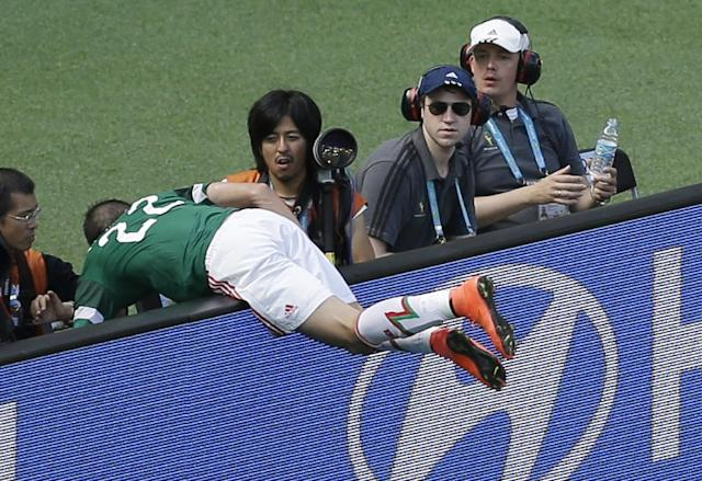 Mexico's Paul Aguilar sits on an advertisement board during the World Cup round of 16 soccer match between the Netherlands and Mexico at the Arena Castelao in Fortaleza, Brazil, Sunday, June 29, 2014. (AP Photo/Themba Hadebe)