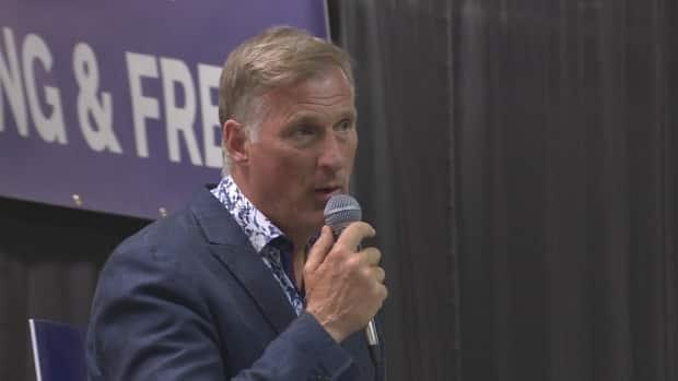 People's Party of Canada Leader Maxime Bernier speaks to supporters at a community hall in Cochrane, Alta., on Monday evening, joiningBanff-Airdrie ridingcandidate Nadine Wellwoodas they hosted town halls there and in Airdrie.  (CBC - image credit)
