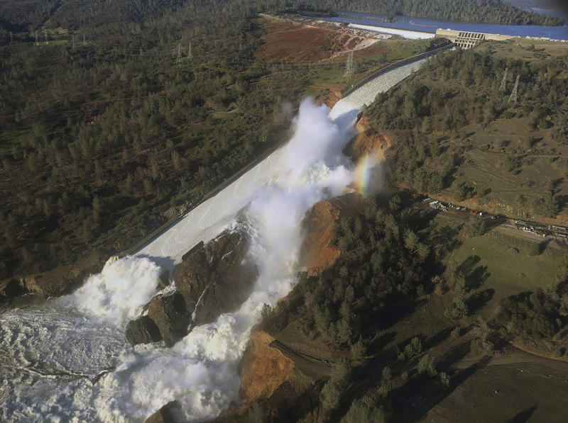 FILE - This Feb. 11, 2017, file aerial photo released by the California Department of Water Resources shows the damaged spillway with eroded hillside in Oroville, Calif. One year after the closest thing to disaster at a major U.S. dam in a generation, federal dam regulators say they are looking hard at how they overlooked the built-in weaknesses of old dams like California's Oroville Dam for decades, and expect dam managers around the country to study their old dams and organizations equally hard. (William Croyle/California Department of Water Resources via AP, File)