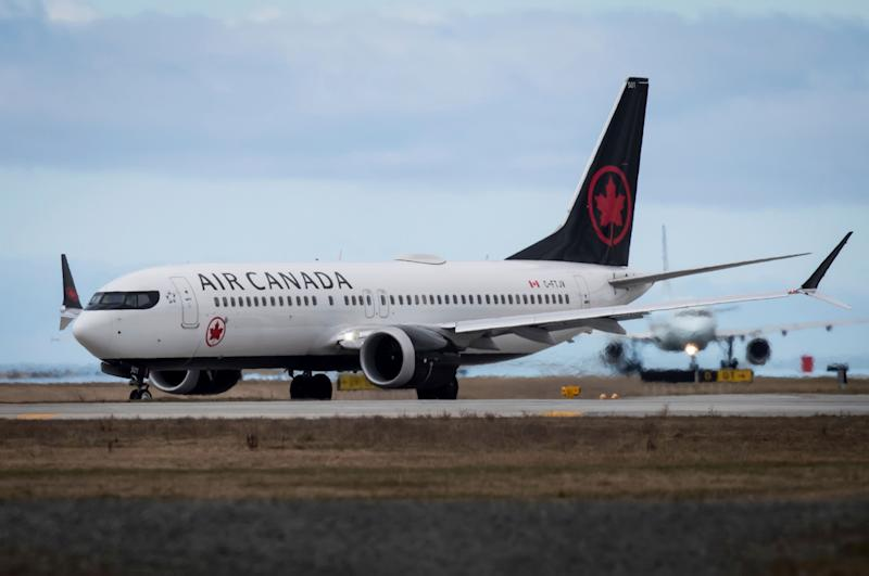 """An Air Canada Boeing 737 Max 8 aircraft departing for Calgary taxis to a runway at Vancouver International Airport in Richmond, British Columbia on Tuesday, March 12, 2019. Canadian Transport Minister Marc Garneau says """"all options are on the table"""" with regard to the country's fleet of Boeing 737 Max 8 aircraft but says the government currently has no plans to order the grounding of the plane. (Darryl Dyck/The Canadian Press via AP)"""