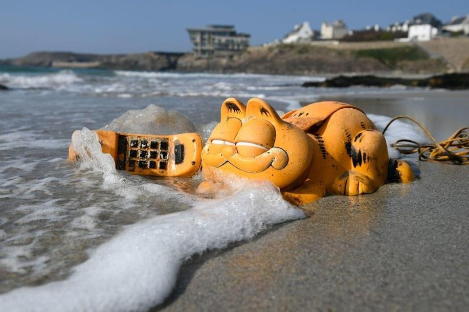 A phone shaped like Garfield the cat sitting in the tides and sea foam on a beach