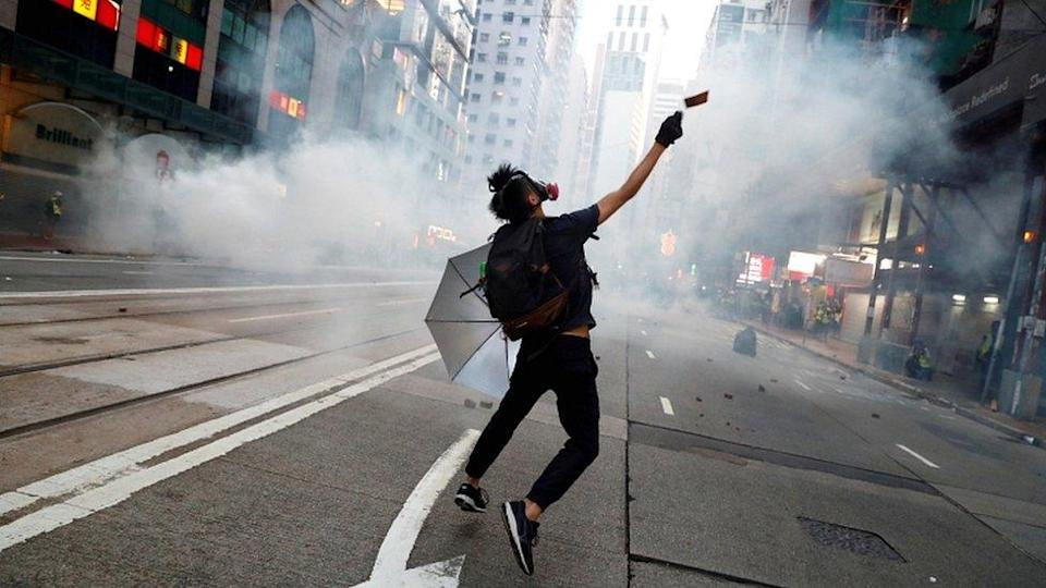 "An anti-government protester reacts as police fire tear gas during a march billed as a global ""emergency call"" for autonomy, in Hong Kong, China, on 2 November 2019"